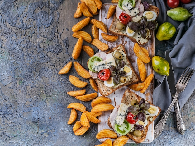 Appetizing toasts with avocado, quail eggs, tomatoes, dor blue cheese and french fries.