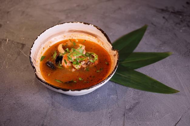 Аппетитный суп том ям конг в белой миске на сером фоне с листьями бамбука.
