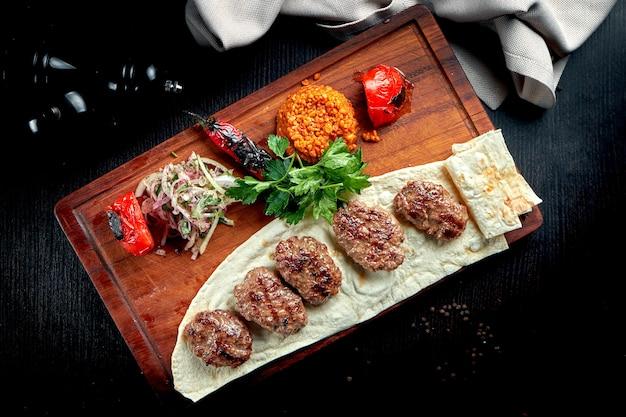불구 루와 구운 야채 장식으로 나무 판에 양고기로 만든 식욕을 돋우는 터키 커틀릿