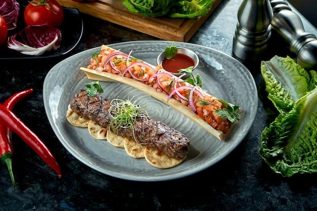 Аппетитный турецкий люля-кебаб из баранины с томатным тартаром и красным соусом, подается в серой тарелке. стол из темного мрамора. шашлык из мяса, ресторанное питание.