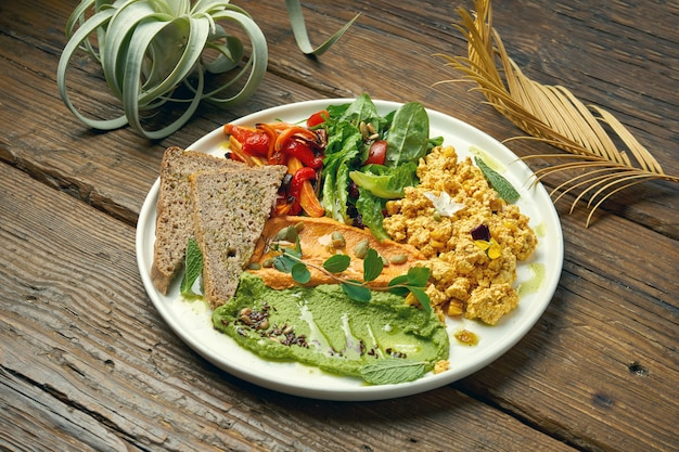 An appetizing vegetarian dish is scramble from tofu cheese, a salad of baked peppers and arugula and two types of hummus. wood table