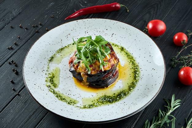 食欲をそそる菜食主義の食糧-木製の表面のセラミックプレートにペストソースとオリーブオイルで焼きたてのナス。食べ物を閉じる