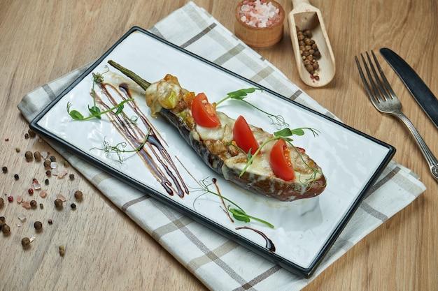 食欲をそそるベジタリアン料理-焼きナスのペストソースとオリーブオイルと木製のテーブルのセラミックプレート。食べ物を閉じる