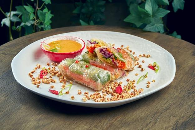 白い皿に野菜とホットソースの食欲をそそるベジタリアン春巻き