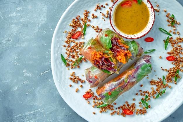 白いプレートに食欲をそそるベジタリアン春巻きと野菜とホットソース