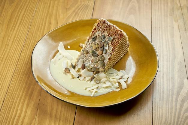 練乳、カスタード、ココナッツチップスを使った食欲をそそるワッフルケーキ。美味しいデザート。木の背景