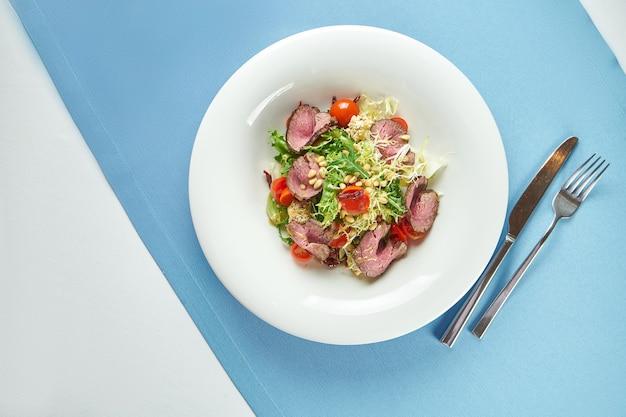 Аппетитный теплый салат с ростбифом, помидорами черри, пармезаном и кедровыми орешками в белой тарелке на синей скатерти