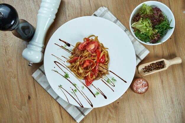Аппетитная вок лапша с помидорами и курицей в белой тарелке на деревянном столе. ресторан в стиле стрит-фуд. крупным планом вид