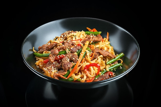 Appetizing wok udon noodles with beef, bell pepper, asparagus, sesame seeds in a black bowl on a black surface with reflection. asian street food