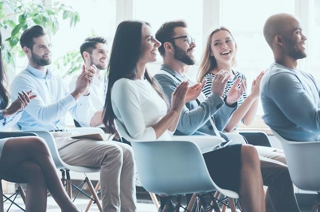그들의 업적에 박수를 보냅니다. 함께 회의에 앉아 박수를 보내는 젊은 쾌활한 사람들의 측면 보기