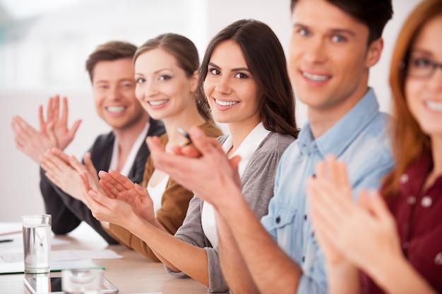 Аплодирую вам. группа молодых людей, сидящих за столом и аплодирующих вам
