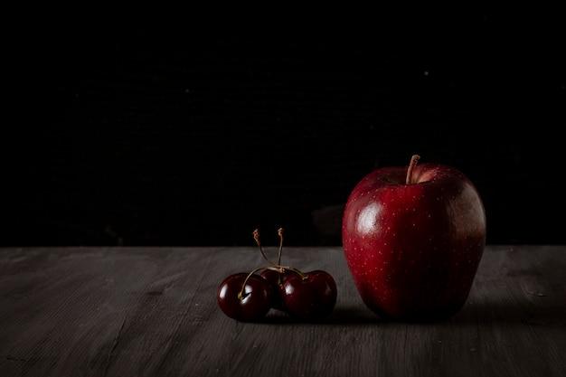ヴィンテージの黒いテーブルにさくらんぼを添えたアップルテキスト用のスペース