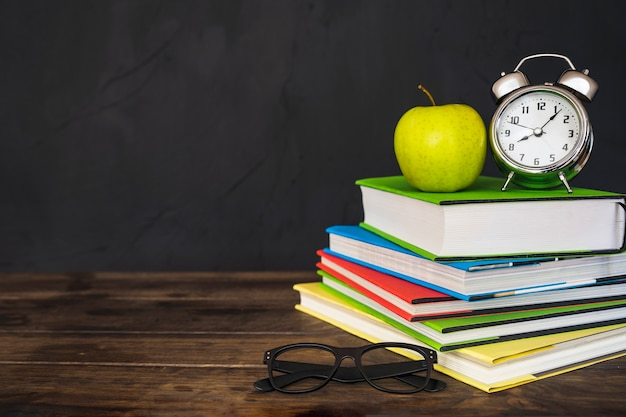 Apple and alarm clock on books with glasses on table