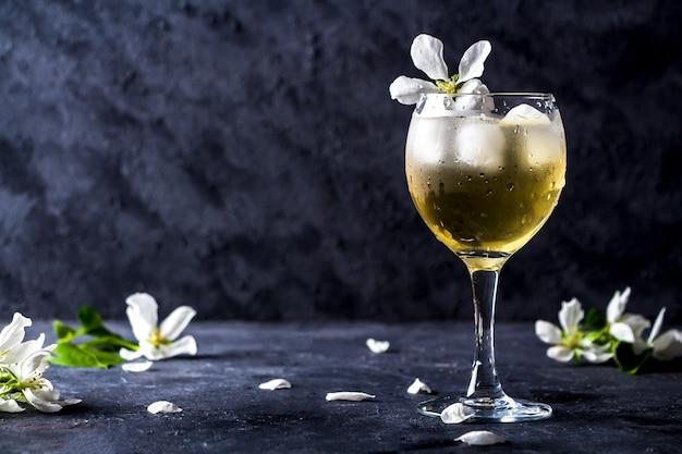 暗い背景にガラスのスパークリングワインとアップルアルコールカクテル。りんごの木の花びらで飾られたさわやかな涼しい夏の飲み物、レモネードまたはアイスティー。