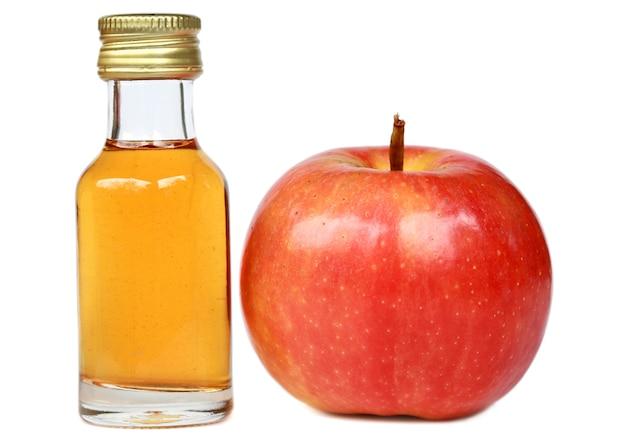 흰색 바탕에 유리병에 있는 사과와 사과 사이다 식초