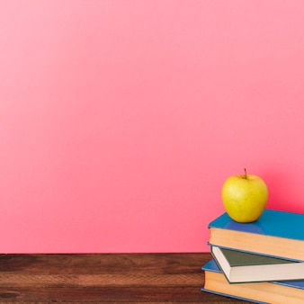 Apple and books near pink wall