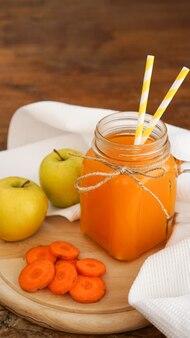 ガラスのリンゴとにんじんジュース、木製の背景に新鮮な野菜や果物。素朴なスタイル。ビタミン入りの自家製ドリンク。縦の写真