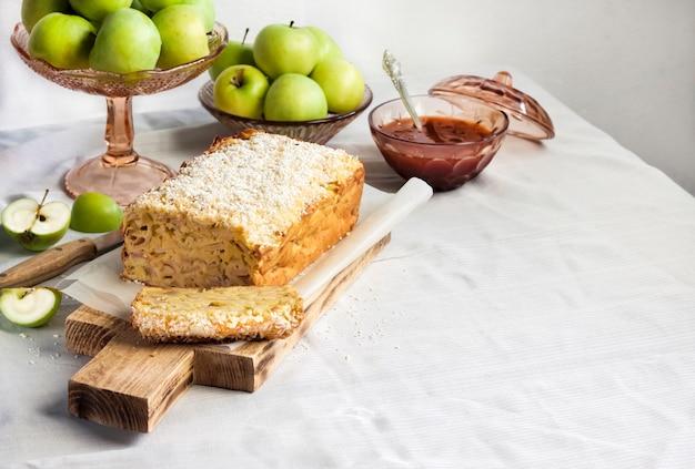 テーブルの上の花瓶にリンゴとココナッツのパンのケーキとリンゴ。コピースペース