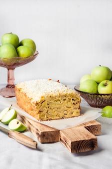 木製のまな板にリンゴとココナッツのオークケーキ、花瓶にリンゴ。コピースペース