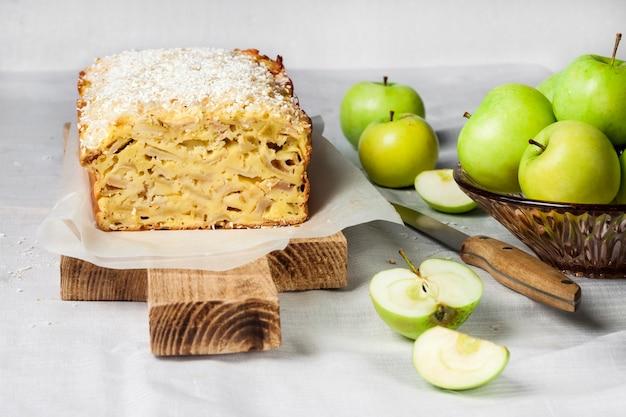 木製のまな板にリンゴとココナッツのオークケーキと花瓶にリンゴ