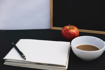 Apple and coffee near notepad
