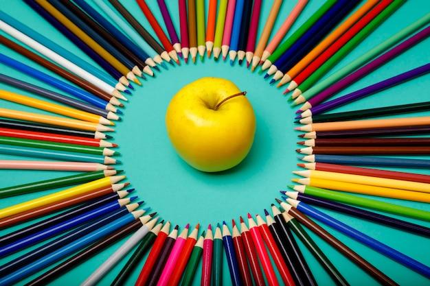 사과와 색연필은 파란색 테이블에 동그라미로 뻗어 있습니다.