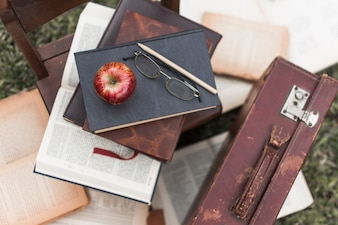 Apple and glasses on books near suitcase