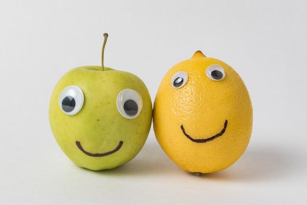 変な顔のリンゴとレモン動眼と笑顔。真の友情の概念。