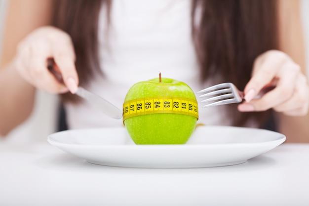 Яблоко и мерной лентой на тарелке.