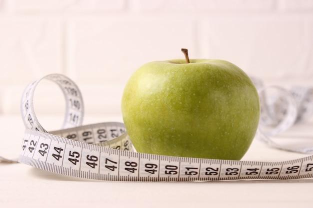 밝은 배경에 사과와 측정 테이프 근접 촬영