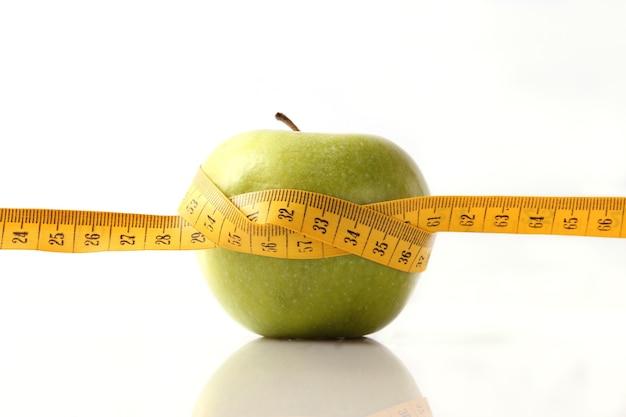 Яблоко и измерительная лента крупным планом на светлом фоне