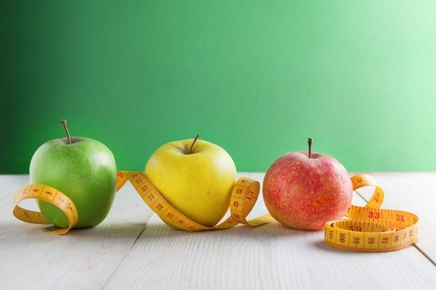 緑の背景にリンゴと巻尺