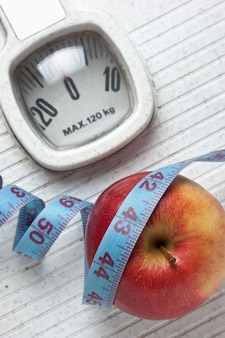 アップルと白で隔離されるフロアスケールの測定テープ