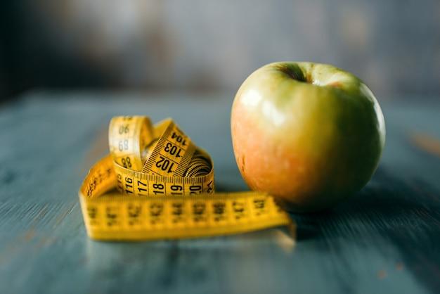 Яблоко и измерительная лента на крупном плане деревянного стола. концепция диеты для похудения, сжигание жира