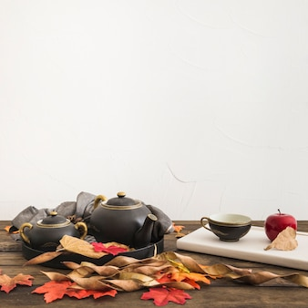 Apple and notebook near tea set and leaves