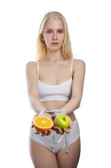 Яблоко и апельсин в женских руках, перевязанных бирюзовой измерительной лентой, изолированы на белой стене как символ фруктовой диеты, здорового питания и витаминной пищи
