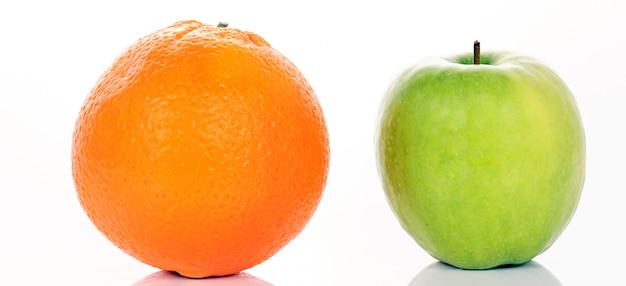 リンゴとオレンジが白いパノラマ写真に分離