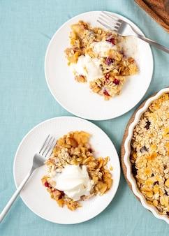 Крошка из яблок и груш с штрейзелем для мороженого, две тарелки с яблочным кобблером, вид сверху вертикальный