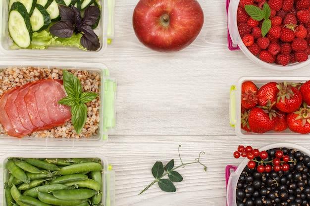 Яблочные и пластиковые контейнеры для приготовления еды со свежей клубникой, малиной, гречневой кашей.