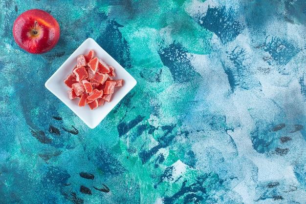 Яблоко и красный мармелад в миске на синем столе.