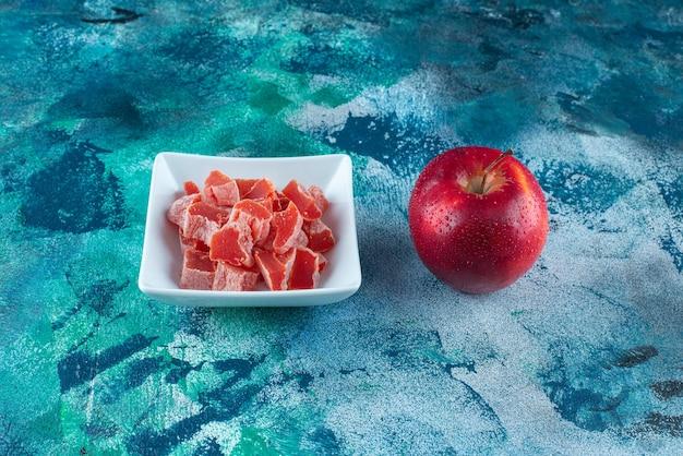 파란 테이블에 있는 그릇에 사과와 빨간 마멀레이드.