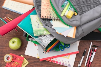 Apple and stationery near schoolbag