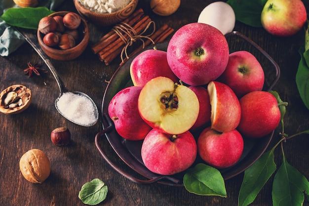 素朴な木製のテーブルにアップルパイの季節のコンセプトを焼くアップル