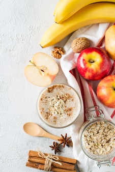 Apple and banana oatmeal smoothie raw helthy breakfast over background whit