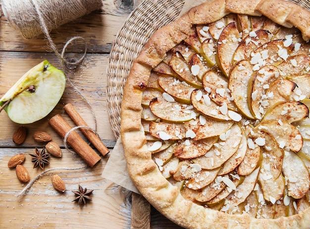 木製のシナモンとアーモンドとアップルビスケットパイ