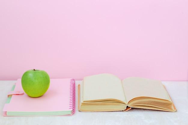 Яблоко, книга, тетрадь на столе на розовом фоне
