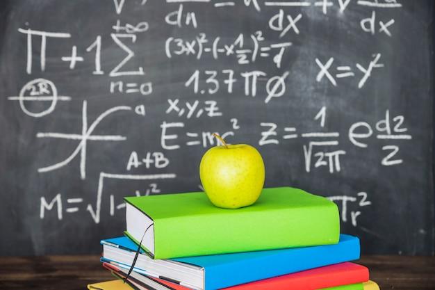 Apple on books pile near chalkboard
