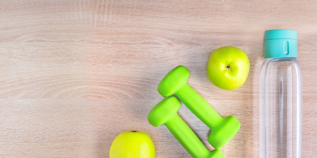 Apple, bottle of water and dumbbells on wooden background with copy space. concept healthy lifestyle, healthy food, sport and diet.