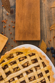 Apple cake near chopping board between foliage and berries
