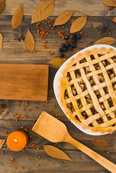Apple cake near cutting board between foliage and berries